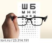 Купить «Очки для зрения на фоне проверочной таблицы», фото № 23314191, снято 22 июля 2016 г. (c) Veaceslav Cernat / Фотобанк Лори
