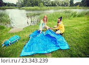 happy couple setting up tent outdoors. Стоковое фото, фотограф Syda Productions / Фотобанк Лори