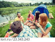 happy friends eating watermelon at camping. Стоковое фото, фотограф Syda Productions / Фотобанк Лори