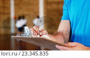 Купить «Sports teacher writing on clipboard», видеоролик № 23345835, снято 4 апреля 2020 г. (c) Wavebreak Media / Фотобанк Лори