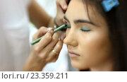 Купить «Визажист делает модели красивый макияж, парикмахер делает прическу», видеоролик № 23359211, снято 5 августа 2016 г. (c) Константин Шишкин / Фотобанк Лори