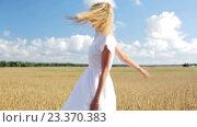 Купить «smiling young woman in white dress on cereal field», видеоролик № 23370383, снято 6 августа 2016 г. (c) Syda Productions / Фотобанк Лори