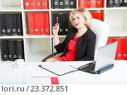 Купить «Улыбающаяся женщина-предприниматель сидит в офисе за письменным столом», фото № 23372851, снято 18 июня 2016 г. (c) Сергей Дубров / Фотобанк Лори
