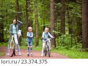 Купить «Прогулка на велосипедах и роликах. Молодая женщина с дочерьми в парке», фото № 23374375, снято 9 июля 2016 г. (c) Дмитрий Травников / Фотобанк Лори