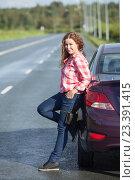 Купить «Симпатичная девушка в красной клетчатой рубашке стоит у машины на дороге», фото № 23391415, снято 12 августа 2016 г. (c) Кекяляйнен Андрей / Фотобанк Лори