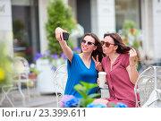 Купить «Две молодые девушки делают сэлфи в кафе на открытом воздухе», фото № 23399611, снято 18 июня 2016 г. (c) Дмитрий Травников / Фотобанк Лори