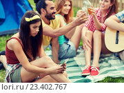 Купить «young woman with smartphone and friends at camping», фото № 23402767, снято 25 июля 2015 г. (c) Syda Productions / Фотобанк Лори