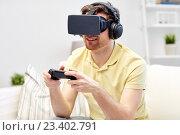 Купить «man in virtual reality headset with controller», фото № 23402791, снято 12 марта 2016 г. (c) Syda Productions / Фотобанк Лори