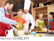 Купить «happy friends and chef cook baking in kitchen», фото № 23402911, снято 12 февраля 2015 г. (c) Syda Productions / Фотобанк Лори