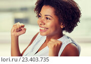 Купить «happy african young woman with raised fists», фото № 23403735, снято 8 июля 2015 г. (c) Syda Productions / Фотобанк Лори