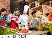 happy friends and chef cook cooking in kitchen. Стоковое фото, фотограф Syda Productions / Фотобанк Лори
