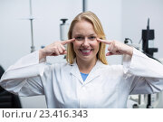 Купить «Female optometrist pointing at her eyes», фото № 23416343, снято 19 июня 2016 г. (c) Wavebreak Media / Фотобанк Лори