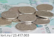 Купить «Рублевые монеты номиналом в 1, 2 и 5 рублей на фоне купюр в 1000 рублей», фото № 23417003, снято 20 августа 2016 г. (c) E. O. / Фотобанк Лори
