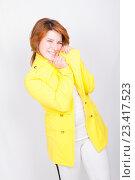 Купить «Рыжая девушка в желтым жакете с непонятным выражением лица», фото № 23417523, снято 11 февраля 2016 г. (c) Emelinna / Фотобанк Лори