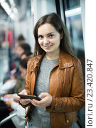 Купить «brunette girl using cell phone and smiling at subway», фото № 23420847, снято 23 июля 2019 г. (c) Яков Филимонов / Фотобанк Лори