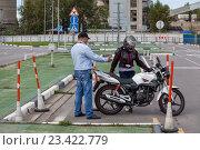 Купить «Обучение езде на мотоцикле на площадке, парковка мотоцикла в гараж», фото № 23422779, снято 19 августа 2016 г. (c) Кекяляйнен Андрей / Фотобанк Лори