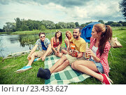 happy friends with drinks and guitar at camping. Стоковое фото, фотограф Syda Productions / Фотобанк Лори