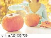 Купить «close up of woman carving pumpkins for halloween», фото № 23433739, снято 17 сентября 2014 г. (c) Syda Productions / Фотобанк Лори