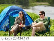 Купить «happy couple drinking beer at campsite tent», фото № 23434199, снято 27 мая 2016 г. (c) Syda Productions / Фотобанк Лори