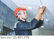 worker installing smoke detector on the ceiling. Стоковое фото, фотограф Дмитрий Калиновский / Фотобанк Лори