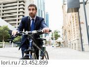 Купить «Young businessmen with a bike», фото № 23452899, снято 4 апреля 2015 г. (c) Sergey Nivens / Фотобанк Лори