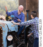Купить «Two drivers working with tractor», фото № 23462339, снято 24 августа 2019 г. (c) Яков Филимонов / Фотобанк Лори