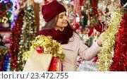 Купить «woman choosing Christmas decoration», видеоролик № 23472755, снято 2 декабря 2015 г. (c) Яков Филимонов / Фотобанк Лори