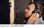 Купить «man with headphones singing at recording studio», видеоролик № 23498939, снято 25 августа 2016 г. (c) Syda Productions / Фотобанк Лори