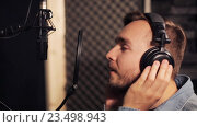 Купить «man with headphones singing at recording studio», видеоролик № 23498943, снято 25 августа 2016 г. (c) Syda Productions / Фотобанк Лори