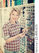 Купить «Mature glad woman customer picking various buttons», фото № 23499615, снято 14 июля 2020 г. (c) Яков Филимонов / Фотобанк Лори