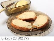 Купить «Хлеб с маслом в тарелке, нож и масленка на белом фоне», эксклюзивное фото № 23502775, снято 8 сентября 2016 г. (c) Яна Королёва / Фотобанк Лори
