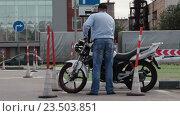 Купить «Инструктор показывает мотоциклисту как нужно заводить мотоцикл в гараж», видеоролик № 23503851, снято 21 августа 2016 г. (c) Кекяляйнен Андрей / Фотобанк Лори