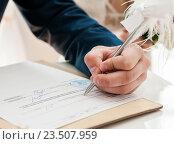 Купить «Жених ставят подпись в документах о заключение брака в ЗАГСе», эксклюзивное фото № 23507959, снято 16 июля 2016 г. (c) Игорь Низов / Фотобанк Лори
