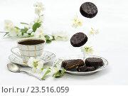 Шоколадное печенье с белым сервизом и цветами на белом фоне. Стоковое фото, фотограф Наталья Чумакова / Фотобанк Лори