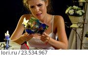 Купить «Unhappy girl burn love photos pictures.4k», видеоролик № 23534967, снято 21 августа 2016 г. (c) Gennadiy Poznyakov / Фотобанк Лори