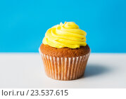 Купить «close up of cupcake or muffin with icing on table», фото № 23537615, снято 30 июня 2016 г. (c) Syda Productions / Фотобанк Лори