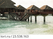 bungalow huts in sea water on exotic resort beach. Стоковое фото, фотограф Syda Productions / Фотобанк Лори