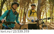 Купить «Mountain biking couple taking a break in the forest», видеоролик № 23539319, снято 20 июля 2019 г. (c) Wavebreak Media / Фотобанк Лори