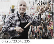 Купить «Mature salesman looking at trowels», фото № 23543235, снято 18 ноября 2018 г. (c) Яков Филимонов / Фотобанк Лори