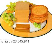 Купить «Brunost - национальный норвежский козий коричневый сыр с сухариками и спелым белым виноградом», фото № 23545911, снято 17 сентября 2016 г. (c) Валерия Попова / Фотобанк Лори