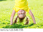 Купить «kid girl standing upside down on her head over grass in summer», фото № 23549735, снято 3 сентября 2015 г. (c) Оксана Кузьмина / Фотобанк Лори