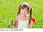 Купить «Happy child on summer grass background with healthy vegetables in hands.», фото № 23549835, снято 3 сентября 2015 г. (c) Оксана Кузьмина / Фотобанк Лори