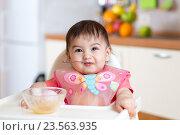 Купить «funny baby child eating itself with spoon in kitchen», фото № 23563935, снято 29 января 2016 г. (c) Оксана Кузьмина / Фотобанк Лори