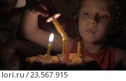 Купить «Slow motion view of small girl lighting the candles on birthday cake in the dark», видеоролик № 23567915, снято 1 июля 2016 г. (c) Данил Руденко / Фотобанк Лори