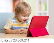 Купить «Cute kid toddler boy with tablet pc», фото № 23569211, снято 17 октября 2015 г. (c) Оксана Кузьмина / Фотобанк Лори
