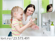 Купить «Happy mother and child washing hands with soap in bathroom», фото № 23573491, снято 2 апреля 2015 г. (c) Оксана Кузьмина / Фотобанк Лори