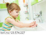 Купить «Cute little girl washing her hands in bathroom», фото № 23574227, снято 31 октября 2014 г. (c) Оксана Кузьмина / Фотобанк Лори