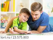 Купить «Father and son read together sitting on the floor. Kid reading story book with his dad at home.», фото № 23575803, снято 4 октября 2014 г. (c) Оксана Кузьмина / Фотобанк Лори