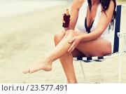 Купить «woman spraying sunscreen oil to her skin on beach», фото № 23577491, снято 6 августа 2015 г. (c) Syda Productions / Фотобанк Лори