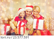 Купить «smiling family holding gift boxes and sparkles», фото № 23577591, снято 26 октября 2013 г. (c) Syda Productions / Фотобанк Лори